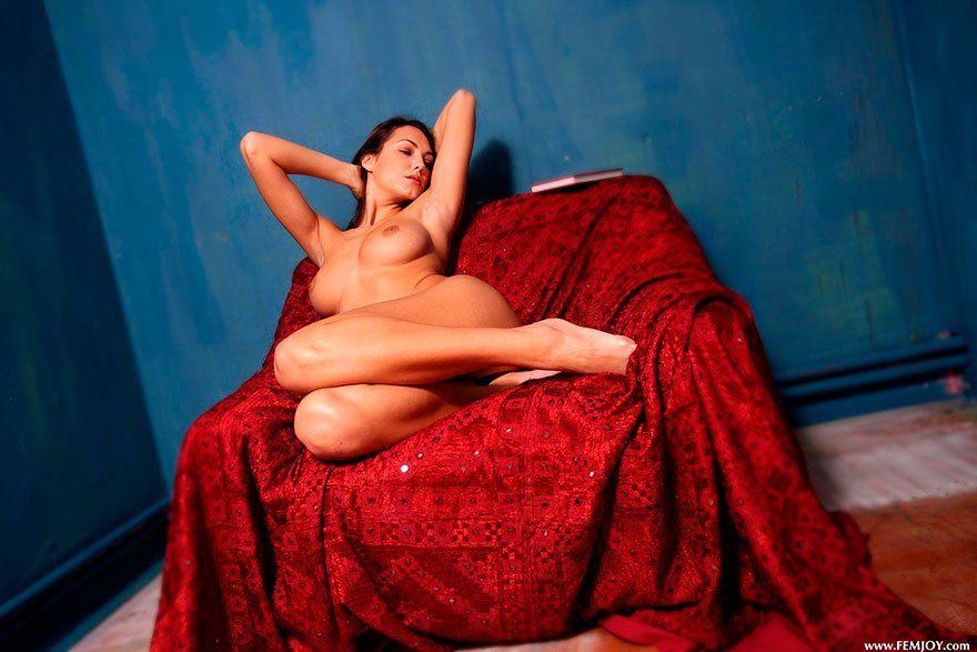 Молодая девушка с красивой грудью сидит на красном покрывале